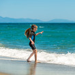 canvas print picture - girl in a wetsuit on the beach