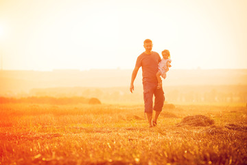 Dad playing with his daughter in a field
