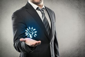 Businessman holding bulb as a concept of new creative idea