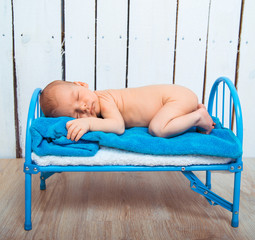 newborn baby sleeps in a small bed