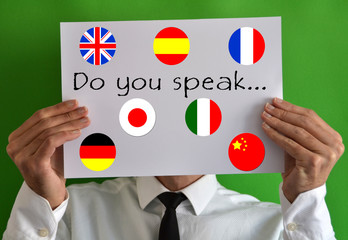 Businessman showing a sheet with text Do you speak and flags