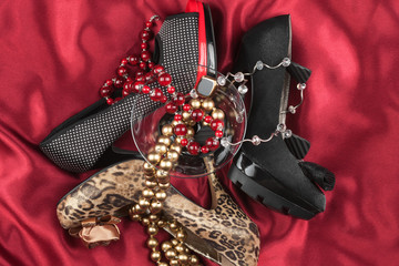 Shoes and glass with beads on a red cloth
