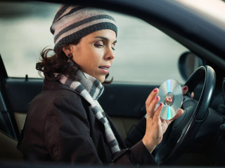 Woman driving and listening music on the cd player