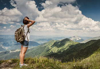 Woman with backpack on the mountain hills