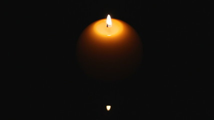 candle on dark water surface