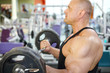 Bodybuilder in black jersey raises big heavy barbell in gym hall