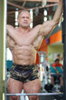 Handsome bodybuilder looks at mirror on his muscles in gym hall