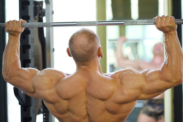 Back of bodybuilder raising barbell in gym hall before mirror