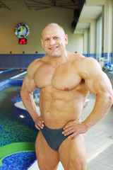 Happy bodybuilder in swimming trunks stands near indoor pool