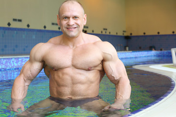 Happy bodybuilder stands in pure water of swimming pool