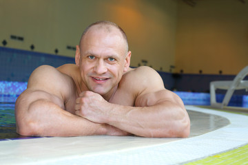 Happy bodybuilder relies on curb of swimming pool of gym hall