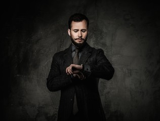 Handsome well-dressed man in jacket looking at wrist watch
