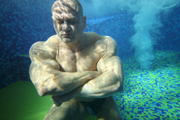 Bodybuilder with closed eyes on bottom of pool underwater