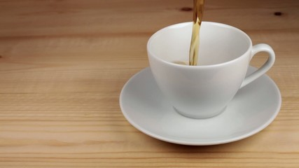 Tea being poured into white tea cup