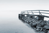 Old wooden pier on the lake in foggy morning