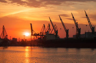 Silhouettes of cranes and industrial cargo ships in Varna port a