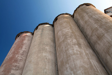 Row of grain silos under deep blue sky