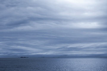 Dark blue stormy cloudy sky. Empty Norwegian Sea landscape backg