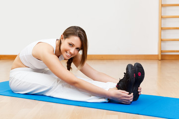 smiling young female stretching on the floor sitting on mat