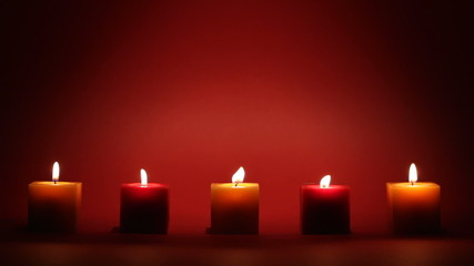 candles in a row on dark background