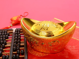 Chinese gold ingot and abacus mean symbols of wealth and prosper