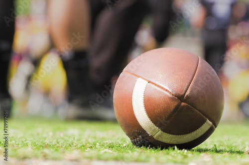 American football ball and de-focused players. poster