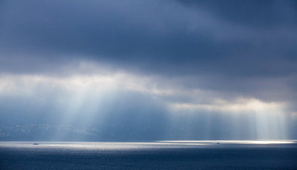 Sunlight goes through dark clouds. Bay of Tangier, Morocco