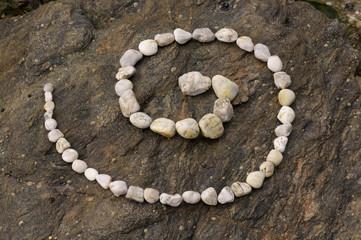 Esoterische Spirale aus hellen Kieseln auf  dunklem Felsblock
