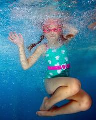 Beautiful girl swims and having fun in water.
