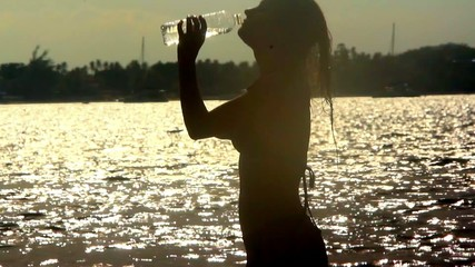 woman drinks water and out of the sea at sunset