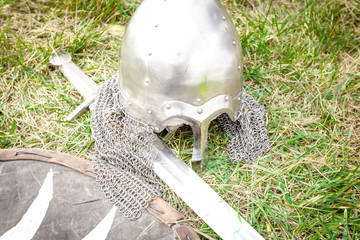 Helmet, sword and shield medieval warrior on the grass