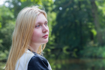 Head of blond girl with water and trees