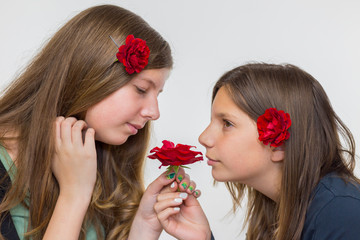 Portrait of two girls smelling roses
