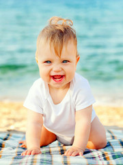 Smiling baby crawling on the beach.