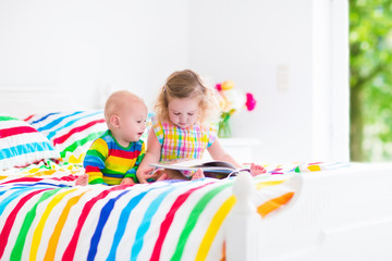 Two pretty children reading a book in bed