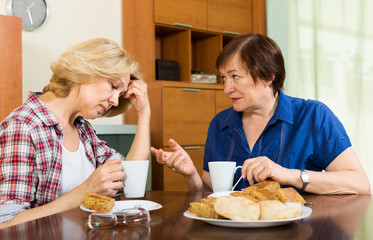 Two mature woman with cup of tea discussing something
