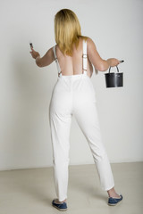 Woman painting wall in bib and braces