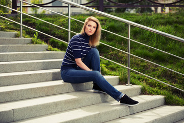 Young fashion woman sitting on the steps