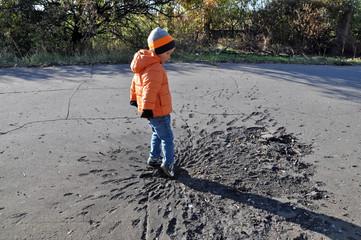 Boy exploring shell crater. Ukraine