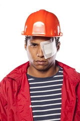 sad dark-skinned worker with helmet and injured eye