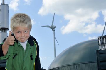 Junge mit Daumen hoch vor Biogasanlage und Windrad