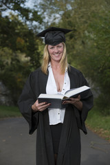 Mature university student in cap and gown reading