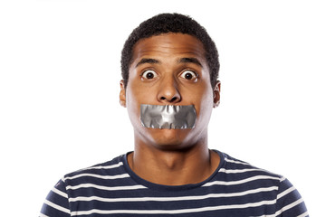 upset dark-skinned young man with adhesive tape over his mouth