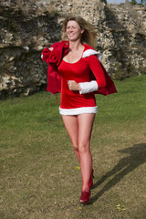 Female Santa running with red sack of Xmas presents