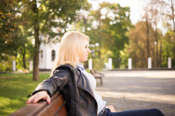 beautiful blond girl sitting on a bench