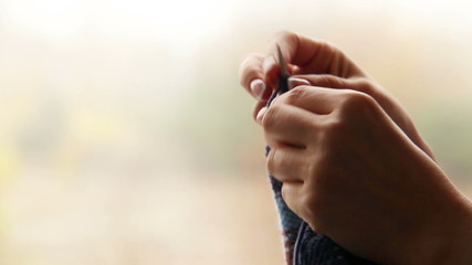 Woman's hands knitting with blurry autumn background