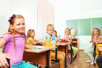 School kids sitting at studying desks in class