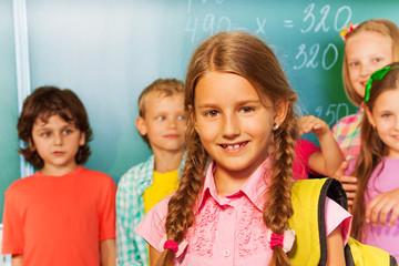 Girl with rucksack on shoulders  near blackboard