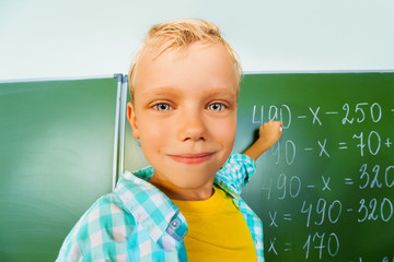 Boy close up view who stands near blackboard