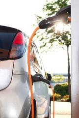 Elektroauto beim Aufladen an Stromtankstelle im Gegenlicht